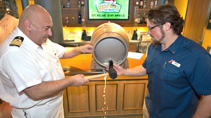 Carnival Vista brewmaster Colin Presby, right, and hotel director Pierre Camilleri tap into the new