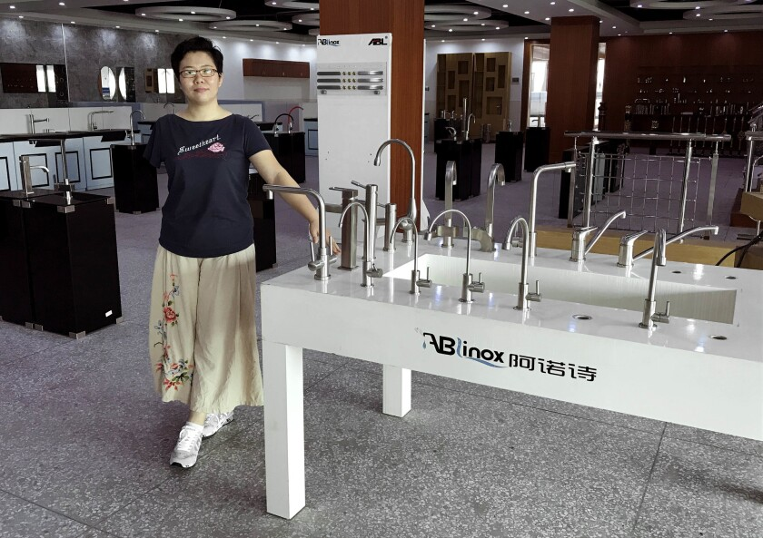 Kate Liang, president of Guangdong ABLinox Sanitaryware company, stands next to models of the kitchen and bathroom fittings her company makes for Chinese and overseas customers. Americans account for one-fifth of her customers, Liang said.