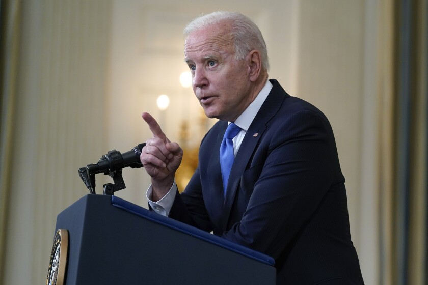 President Biden speaks at a podium and points his finger