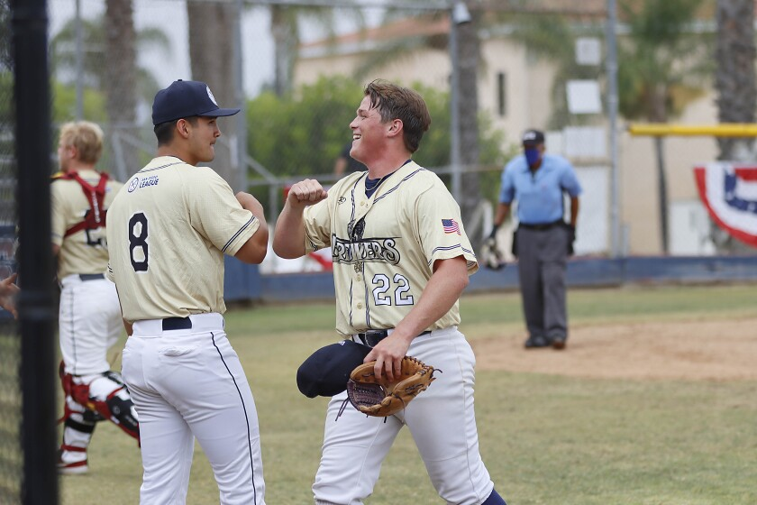 The Warriors' Jansen Lublin (right) gives an elbow bump to teammate Dayton Dooney after Lublin saved the inning on a pop out.
