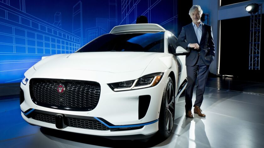 John Krafcik, the chief executive of Waymo, stands with the Jaguar I-Pace. Waymo will buy up to 20,000 of the electric vehicles to help realize its vision for a robotic ride-hailing service.