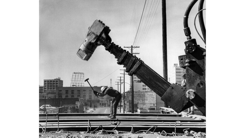 "March 8, 1964: As Manuel Perez takes a swing with an old-fashioned sledgehammer, the new ""woodpecker"" slams down to break concrete on the old Maple Avenue trestle railroad ramp at 6th and Main streets."