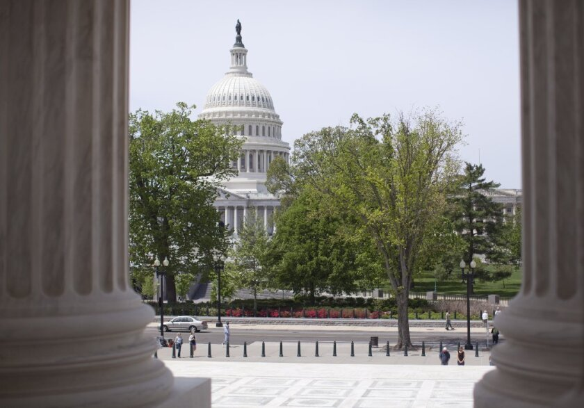 The U.S. Capitol building is seen through the columns on the steps of the Supreme Court in Washington.