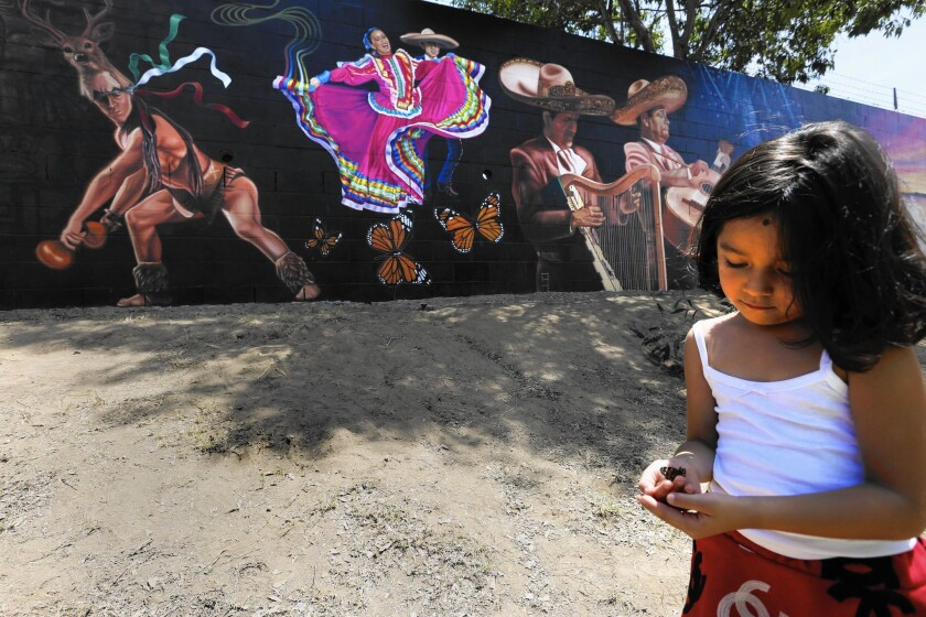 """Long Beach dedicated Jenni Rivera Memorial Park on Thursday to honor the Mexican American singer who died in a plane crash in 2012. Rivera's granddaughter Jaylah Hope Yanez plays with a butterfly near the park's mural, dubbed the """"Mariposa de barrio,"""" the neighborhood butterfly."""