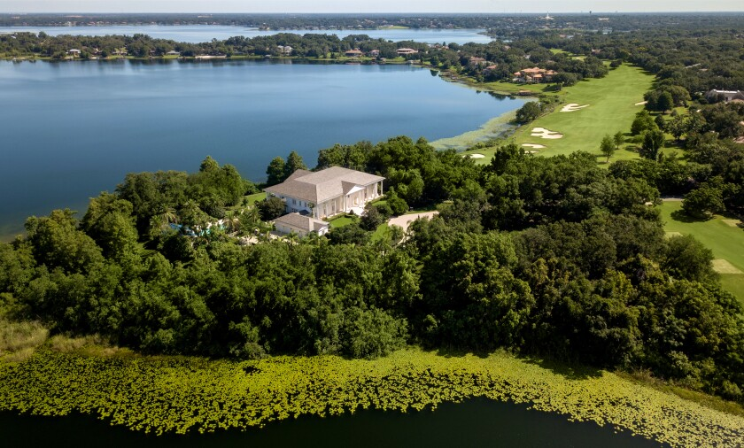 An aerial view shows the 17,000-square-foot mansion surrounded by trees and adjacent to a golf course and the water.