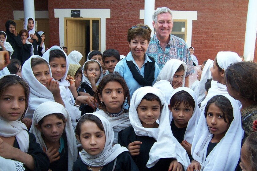 Fary Moini and Steve Brown stand with young students at the school they founded in Jalalabad, Afghanistan in 2004.