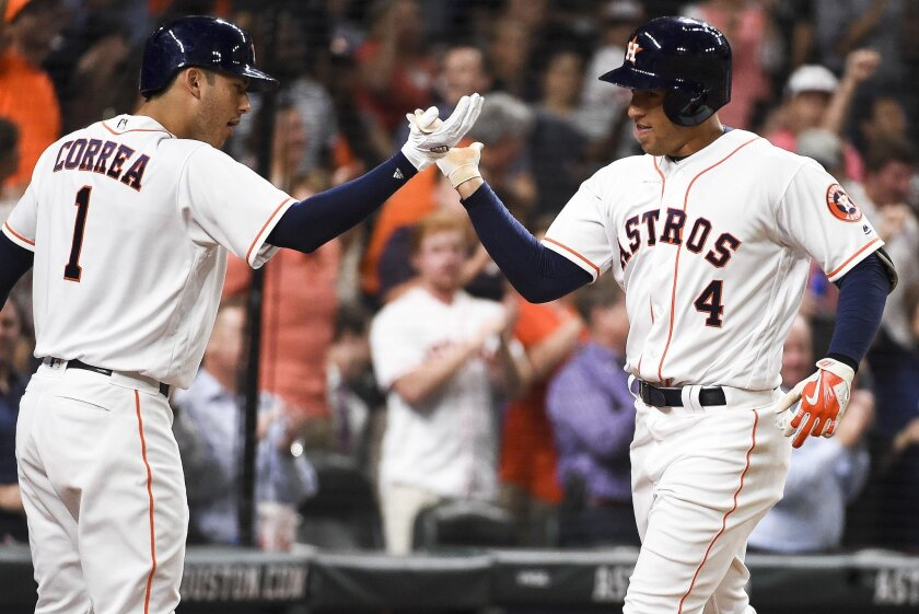Houston Astros' George Springer (4) celebrates his solo home run off Baltimore Orioles starting pitcher Kevin Gausman with Carlos Correa (1) during the fifth inning of a baseball game Thursday, May 26, 2016, in Houston. (AP Photo/Eric Christian Smith)