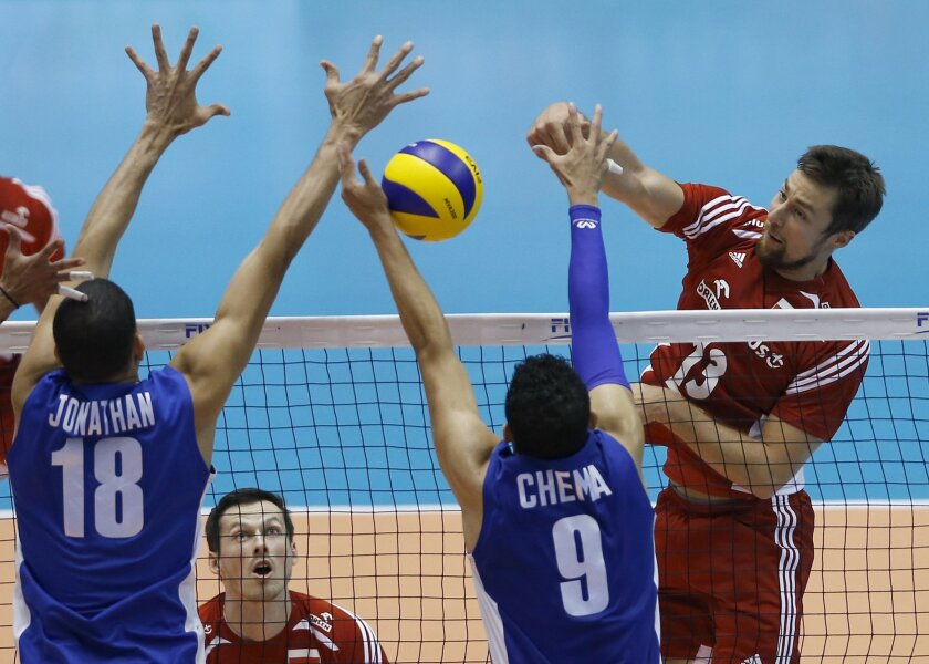 Michal Kubiak of Poland spikes against Jonathan Quijada (18) and Jose Carrasco of Venezuela during the Men's Volleyball World Olympic Qualification Tournament match in Tokyo, Japan, Thursday, June 2, 2016. (AP Photo/Shizuo Kambayashi)