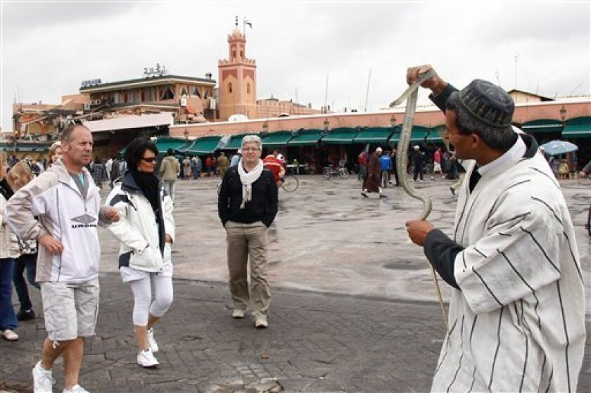 Tourists watch attractions on Djemma el-Fna square, with the Argna cafe in background, in Marrakech, Morocco, Friday, April, 28, 2011, just one day after the explosion. The international police agency Interpol called the attack on a crowded tourist cafe in Marrakech a suspected suicide bombing Friday, as the government said two Canadians, two French citizens, a Dutchman and two Moroccans were among the 15 killed in the explosion. (AP Photo/Abdeljalil Bounhar)