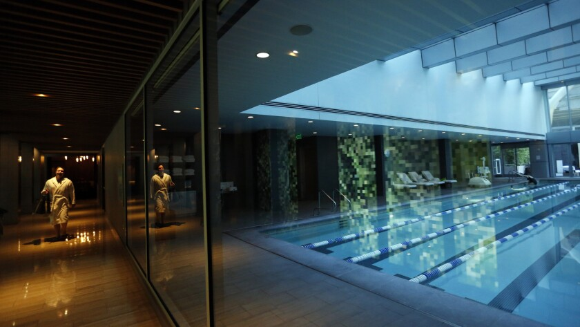A resident of the Millennium Tower walks past the swimming pool that is provided to tenants.
