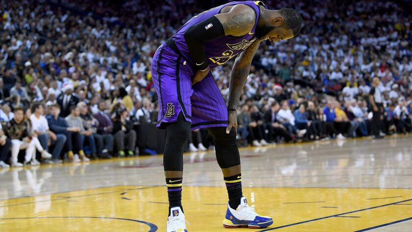 Lakers forward LeBron James (23) leans over in pain after injuring his groin against the Golden State Warriors on Dec. 25.