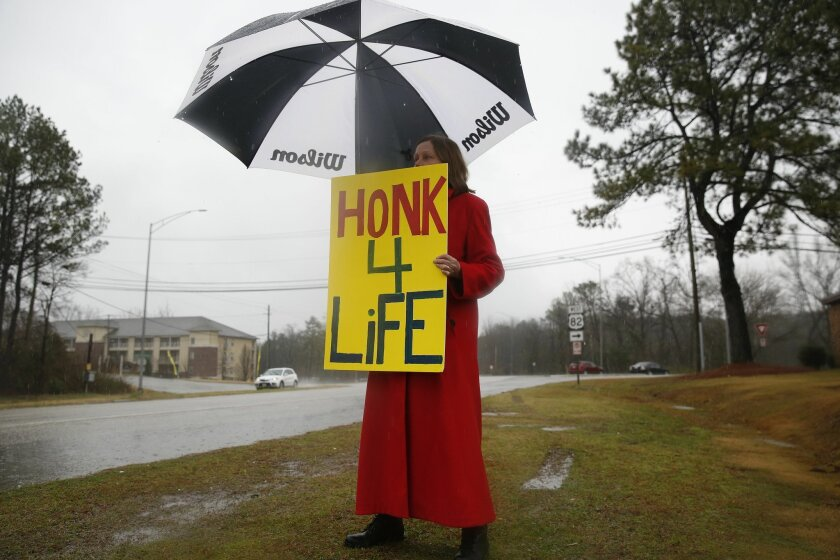 In this photo taken Feb. 22, 2016, Ellie Hermann, stands near the street, protesting the West Alabama Women's Center, in Tuscaloosa, Ala. (AP Photo/Brynn Anderson)