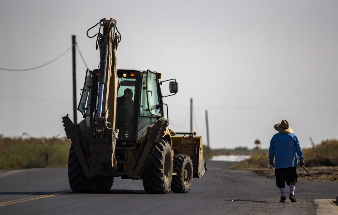 A pedestrian shares the road with a tractor in Stratford.
