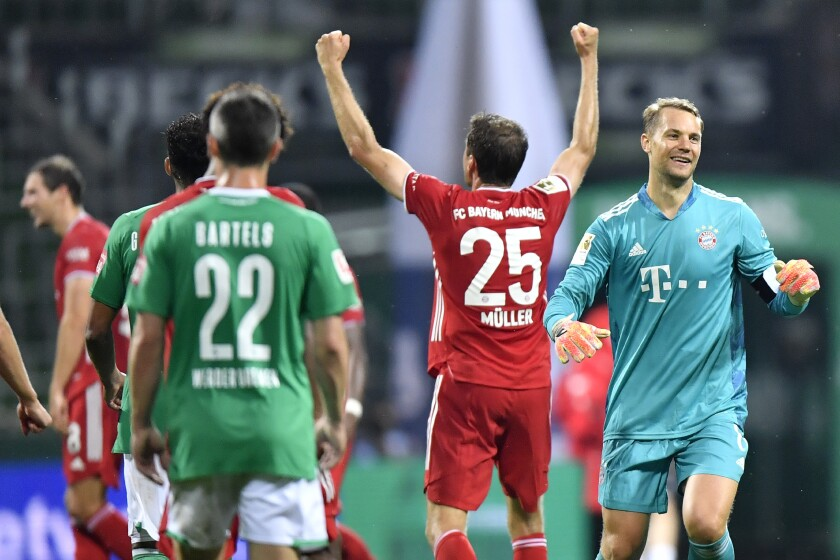 Bayern's goalkeeper Manuel Neuer, right, and Bayern's Thomas Mueller celebrate end of the German Bundesliga soccer match between Werder Bremen and Bayern Munich in Bremen, Germany, Tuesday, June 16, 2020. Because of the coronavirus outbreak all soccer matches of the German Bundesliga take place without spectators. Bayern Munich secured its eighth successive German Bundesliga title Tuesday with two games to spare after beating Werder Bremen 1-0 with a goal from Robert Lewandowski. (AP Photo/Martin Meissner, Pool)