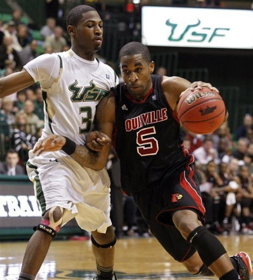 Louisville's Chris Smith, right, drives against South Florida's Hugh Robertson during the first half of an NCAA college basketball game Sunday, Jan. 9, 2011, in Tampa, Fla. (AP Photo/Mike Carlson)