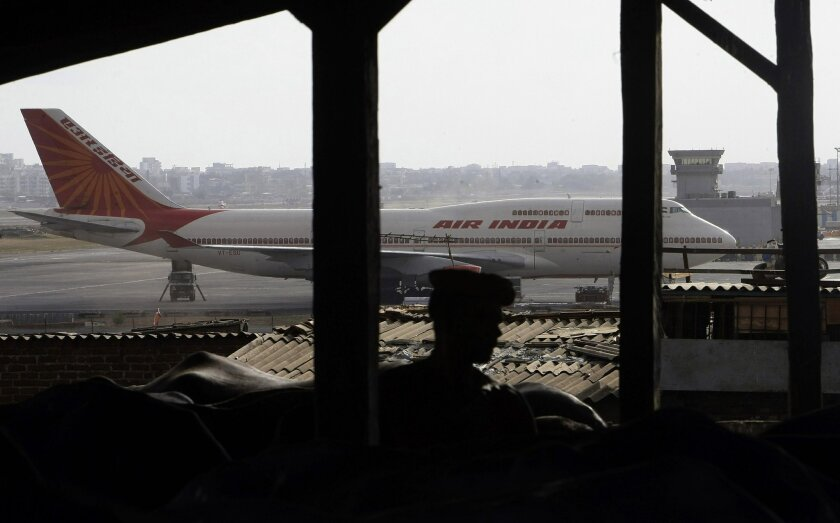 FILE – In this May 25, 2010 file photo, an Air India plane is seen in the background of slums adjoining the the international airport in Mumbai, India. A fast-growing economy and an expanding middle class have made India the world's fastest growing air travel market. The number of passengers grew 2