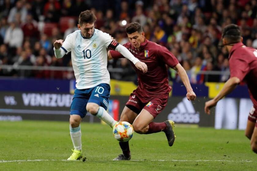 El delantero de la selección de Argentina Leo Messi (i) lucha con Yordan Osorio, de Venezuela, durante el encuentro amistoso que disputan esta noche en el estadio Wanda Metropolitano, en Madrid. EFE/Juan Carlos Hidalgo