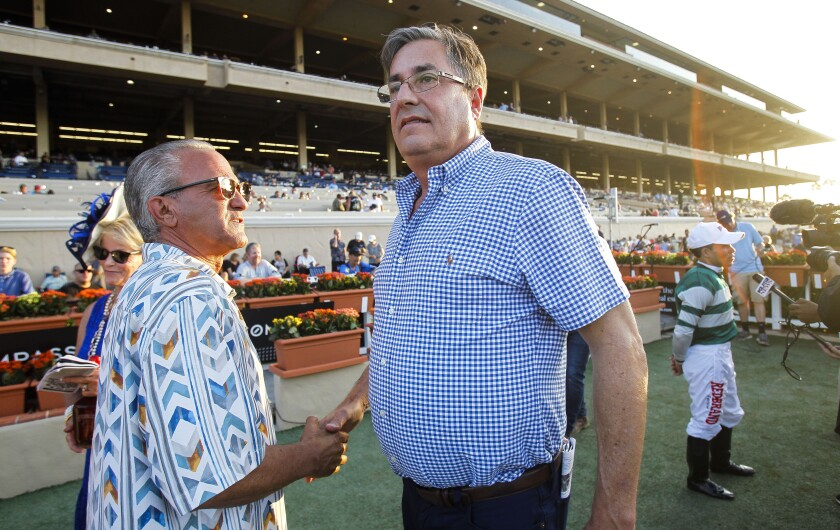 Owner Kosta Hronis, left, shakes horse trainer John Sadler's hand as jockey Joel Rosario is interviewed in the background after their horse Accelerate won the Pacific Classic at Del Mar in 2018.