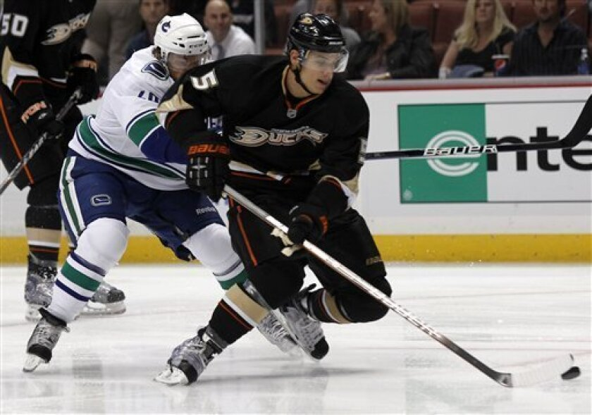 Anaheim Ducks defenseman Luca Sbisa (5) keeps the puck away from Vancouver Canucks center Alexandre Bolduc, left, of Canada, in the first period of a preseason NHL hockey game in Anaheim, Calif., Friday, Oct. 1, 2010. (AP Photo/Lori Shepler)