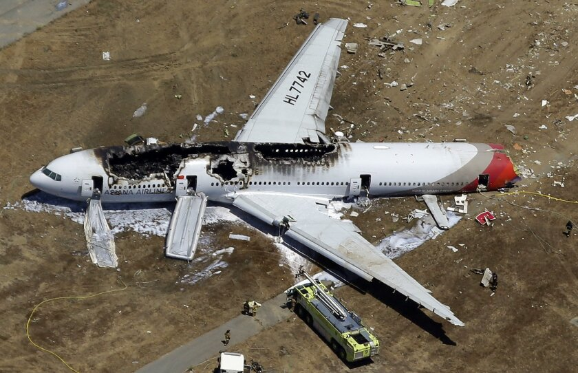 File - In this July 6, 2013, aerial file photo, the wreckage of Asiana Flight 214 lies on the ground after it crashed at the San Francisco International Airport in San Francisco. On Tuesday, March 3, 2015, more than 70 passengers aboard an Asiana Airlines flight that crashed in San Francisco two ye