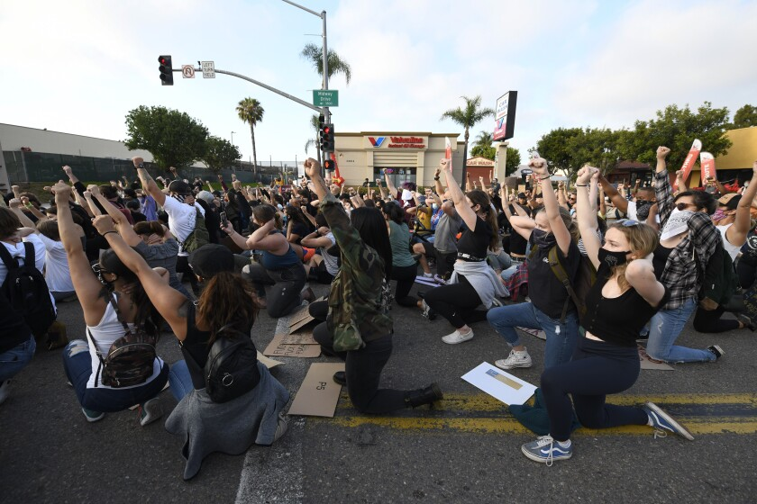 Protesters kneel down as they block Midway Dr. during a Black Lives Matter protest Wednesday, June 3, 2020 in San Diego.