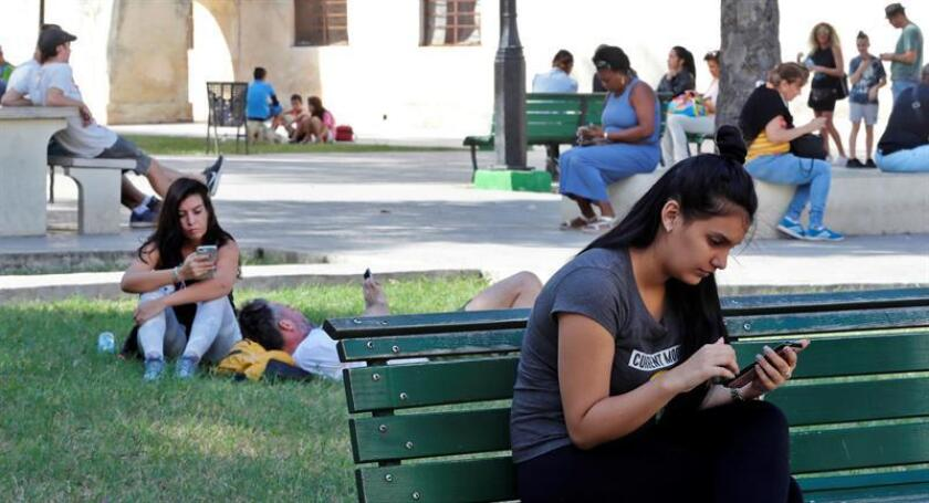 A number of people use the Internet connection on their cell phones in a Havana park with WiFi on Dec. 27, 2018, as Cuba expands access to digital services, which in turn allows Cubans to debate with their leaders on social media, even as the new independent press acts as a civic watchdog. EFE-EPA/Ernesto Mastrascusa