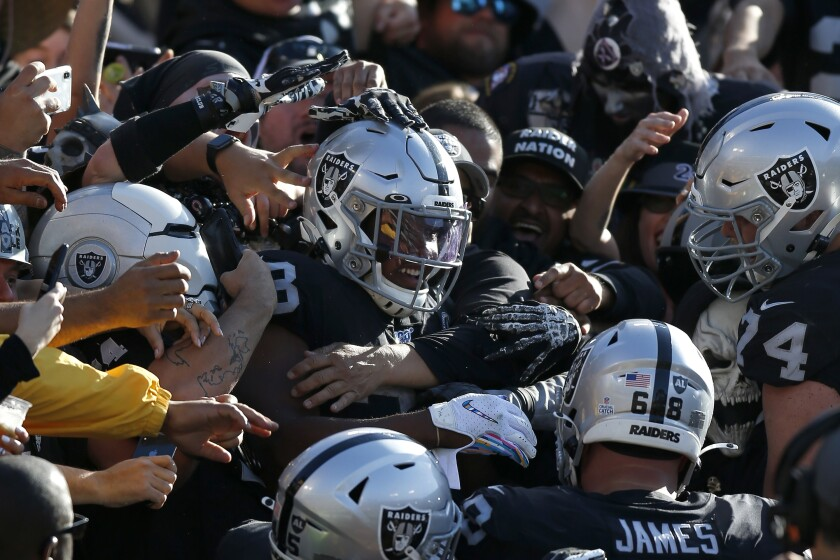 Oakland Raiders running back Josh Jacobs, center, celebrates with teammates and fans after scoring against the Detroit Lions during the first half of an NFL football game in Oakland, Calif., Sunday, Nov. 3, 2019. (AP Photo/D. Ross Cameron)