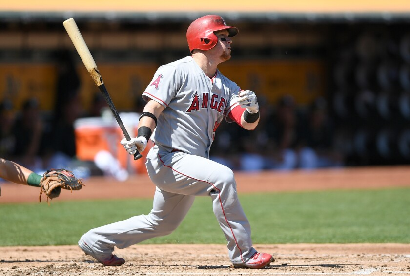 Angels outfielder Kole Calhoun (56) swings and watches the flight of his ball as he hits a solo home run against the Oakland Athletics in the top of the second inning.
