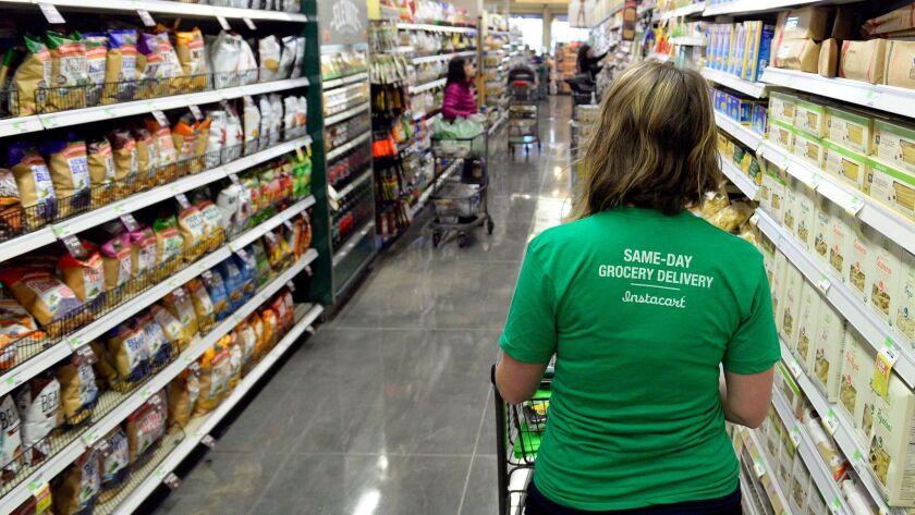 Instacart 'shopper' studies her smartphone as she shops for a customer.