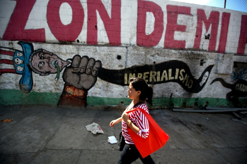 """A pedestrian walks past a mural that reads in Spanish """"Imperialism"""" in Caracas, Venezuela, Thursday, July 17, 2014. Almost four years after Venezuela enacted a law to bar the U.S. from funding groups frequently critical of the socialist government, millions of the American dollars the administratio"""