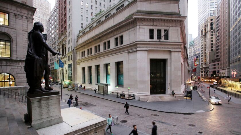 Pedestrians on Wall Street beneath a statue of George Washington.