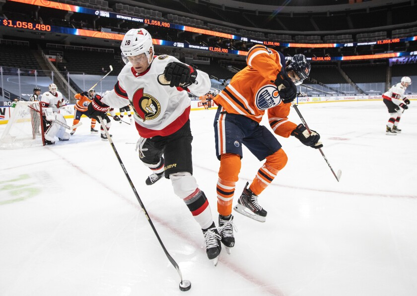 Edmonton Oilers' Jujhar Khaira (16) and Ottawa Senators' Tim Stuetzle (18) battle for the puck during the second period of an NHL hockey game, Wednesday, March 10, 2021 in Edmonton, Alberta. (Jason Franson/The Canadian Press via AP)