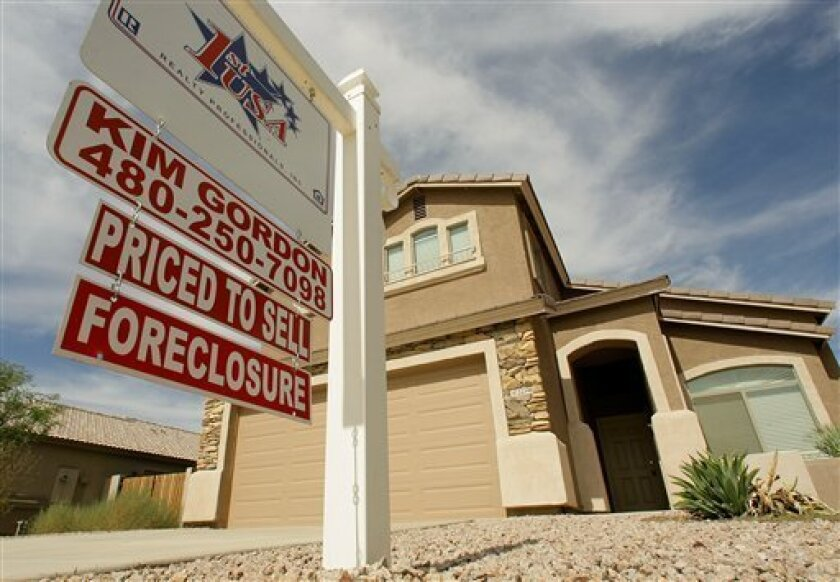 FILE - In this Sept. 26, 2007 file photo, a realty sign stands in front of one of the many homes that are in foreclosure in the Villages of Queen Creek in Queen Creek, Ariz. The number of U.S. homes repossessed by lenders fell to the lowest level in nearly six years last month amid a resurgent housing market and rising home prices, the latest evidence that the nation's foreclosure woes are easing, according to new data from foreclosure listing firm RealtyTrac Inc. (AP Photo/Ross D. Franklin, fil