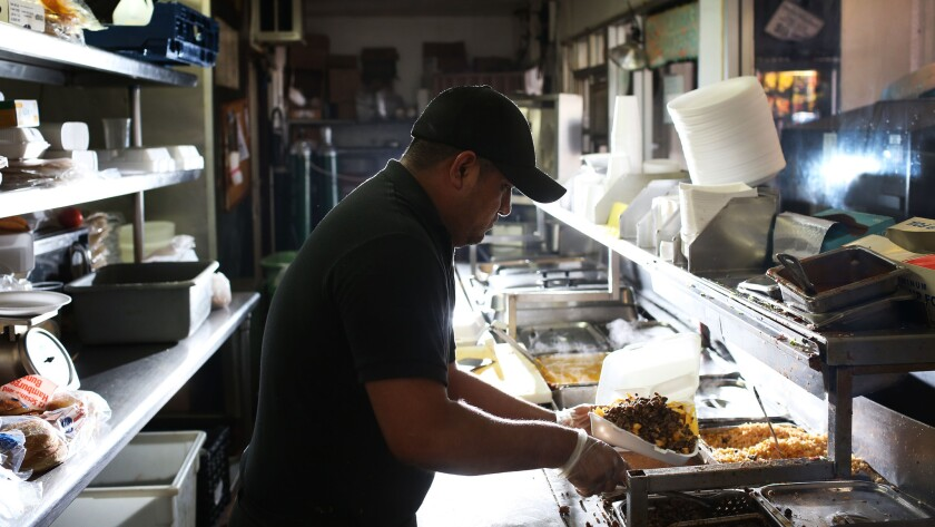 Sebastian Montero, 30, prepares a meal of super fries at Carnitas Michoacan, a 24-hour restaurant in Boyle Heights.