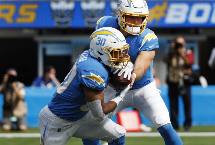 Chargers quarterback Justin Herbert (10) hands off to running back Austin Ekeler against the Cleveland Browns.