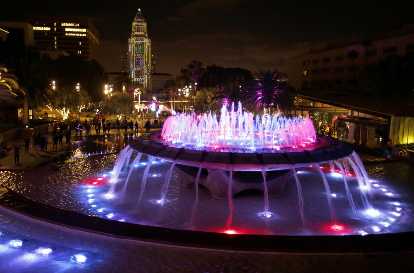 Grand Park's fountain glows with a gleaming City Hall in the background.