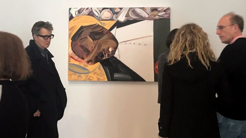 """A group of museum-goers examine a painting entitled """"Open Casket"""" by artist Dana Schutz at the Whitn"""