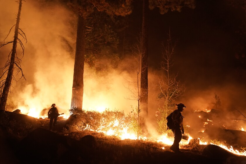 Two firefighters are silhouetted by flames in a burning forest