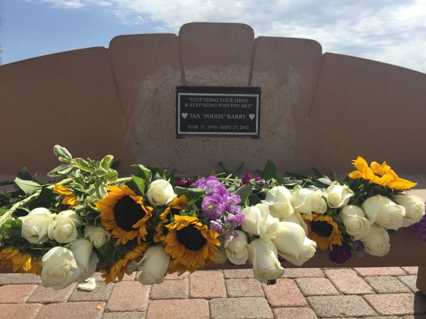 """Flowers cover a bench that's dedicated to Ian """"Poods"""" Barry. Graffiti blacking out Ian's name was removed, and the community has reaffirmed its love for the late skateboarder."""
