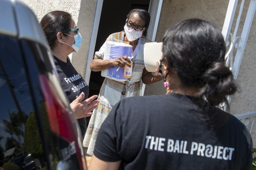 Susie Alexander, center, holds household supplies delivered for her son by Bail Project employees.