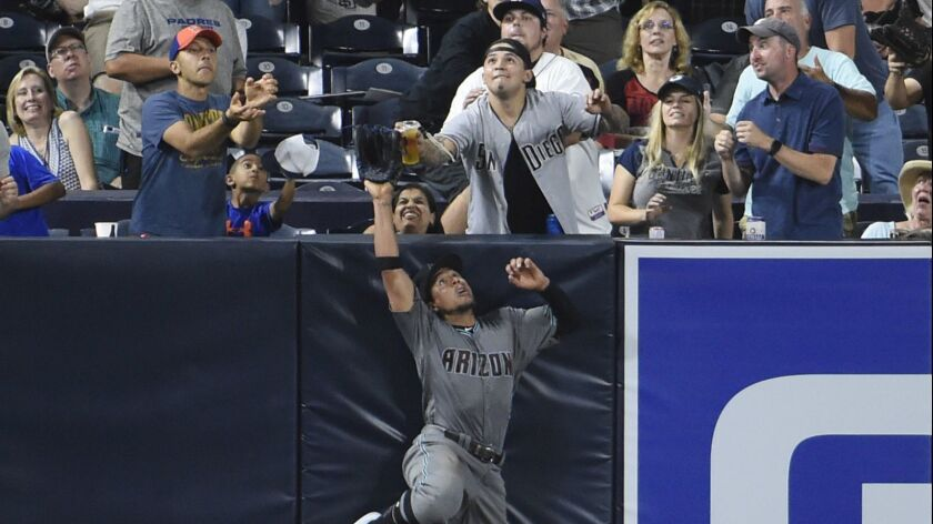 A fan appears to touch Diamondbacks left fielder Jon Jay as he tries for a home run hit by Eric Hosmer.