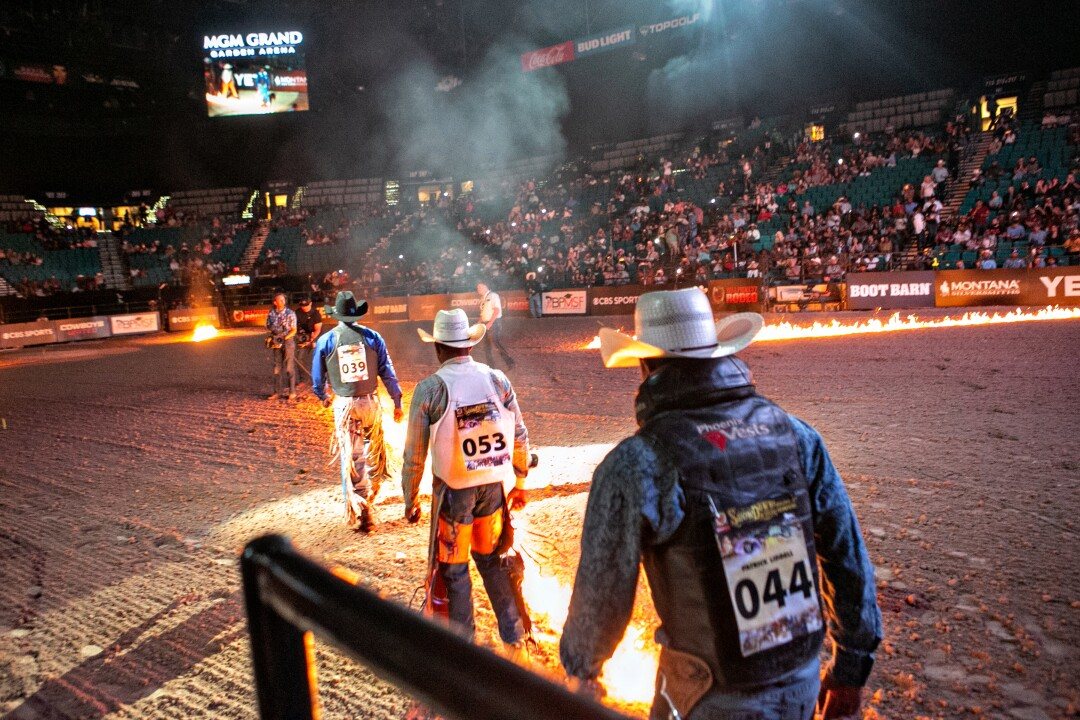 Cowboys walk single file into the arena at the Bill Pickett Invitational Rodeo.