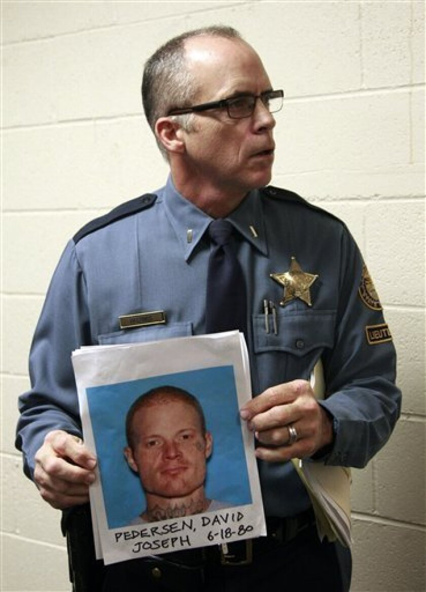 Lt. Gregg Hastings of the Oregon State Police holds a mug shot of David Joseph Pedersen following a news conference Wednesday, Oct. 5 2011, in Salem, Ore. Investigators in a Pacific Northwest manhunt said they have recovered the body of a young adult and have notified the family of a missing Oregon teenager, although the remains have not been positively identified. Authorities have been looking for Cody Myers, 19, of Lafayette, who disappeared after leaving Saturday for a jazz festival on the Oregon coast. The manhunt is focused on David Joseph Pedersen, 31, and his 24-year-old girlfriend, Holly Grigsby, who have been spotted using Myers' car.(AP Photo/Rick Bowmer)