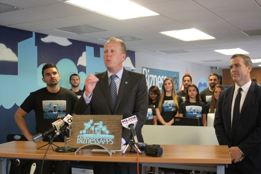 San Diego Mayor Kevin Faulconer helps Bizness Apps open its La Jolla office, while CEO Andrew Gazdecki, San Diego Economic Development Corporation president Mark Cafferty and the Bizness Apps team listen in.