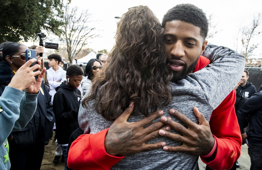 Clippers star Paul George hugs a supporter after unveiling refurbished basketball courts at Domenic Massari Park in Palmdale on Sunday.