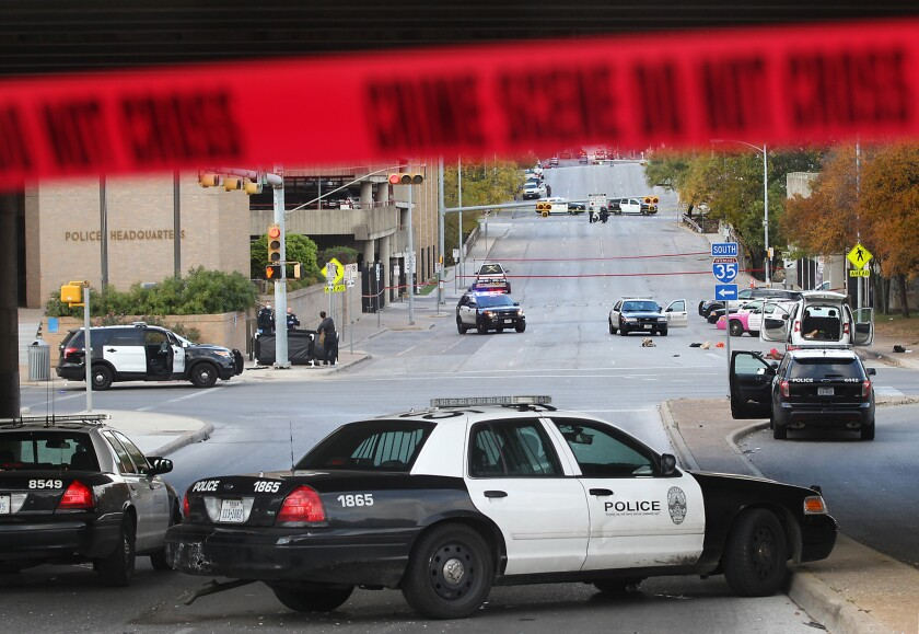 Austin police investigate the scene where an officer shot and killed a man who had shot at least 100 rounds into government buildings.