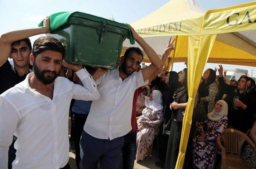 People carry a victim's coffin as they attend funeral services for dozens of people killed in last night's bomb attack targeting an outdoor wedding party in Gaziantep, southeastern Turkey, Sunday, Aug. 21, 2016. The suicide attacker was an Islamic State group child as young as 12 years old. The ext