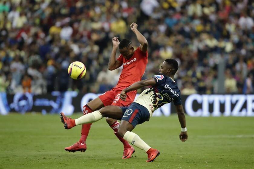 El jugador de América Alex Ibarra (d) pelea por el balón con Luis Quiñones (i), de Toluca durante el juego correspondiente a la jornada 12 del torneo mexicano de fútbol celebrado en el estadio Azteca. EFE