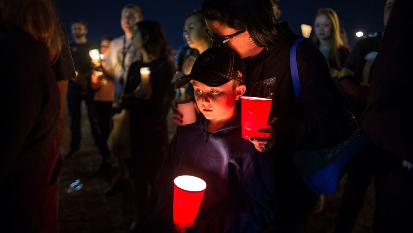 Keli McDade of Las Vegas leans on her son Ayden during a candlelight vigil at Town Square in Las Vegas in tribute to those killed and injured after a gunman opened fire on the Route 91 Harvest festival.