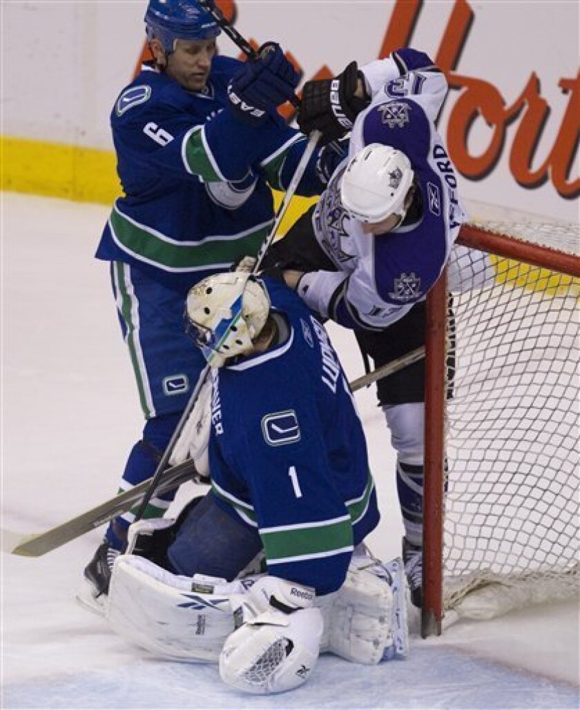 Los Angeles Kings left wing Kyle Clifford (13) tries to get a shot past Vancouver Canucks goalie Roberto Luongo (1) and Vancouver Canucks defenseman Sami Salo (6) during first period NHL hockey action at Rogers arena in Vancouver, British Columbia, Thursday, March 31, 2011.  (AP Photo/The Canadian